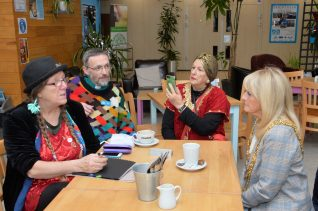 The Mayor and three members of Brighton & Hove Community Radio chatting with a coffee