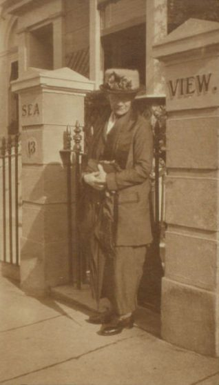 Minnie Taylor dressed in early 20th century style outside her home/boarding house | Jean Calder