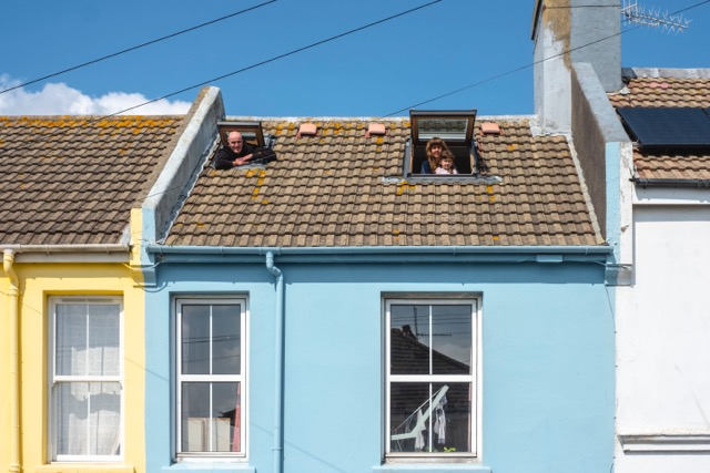 People looking out of velux windows. Photo from series: