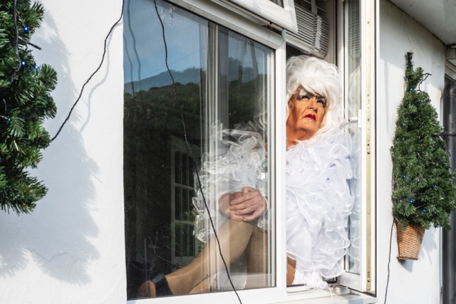 Man in drag sitting in open window. Photo from series: