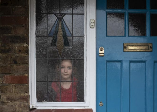 Young girl looking out through stained glass window by front door. From: