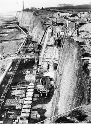 Undercliff Walk and Sea Defences at Ovingdean, c. 1932: Building of Undercliff Walk and sea defences at Ovingdean c.1932. The Undercliff Walk was built in 1930-33 to protect the cliffs east of Black Rock and used 13,000 tons of cement, 150,000 concrete blocks and 500 workers. It was formally opened on 4 July 1933 by the Minister of Health Sir Hilton Young at Ovingdean Gap. Roedean School can be seen in the distance above the cliffs. | Image reproduced with kind permission from Brighton and Hove in Pictures by Brighton and Hove City Council