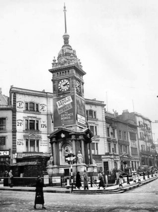Sandbagged Clock Tower, c. 1940: The clock tower at the corner of North Street and Western Road with sandbags and advertisements for