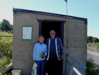 Pam Bean with Bill Burton (both site reps) outside the Tenantry Down shop | Photo by Simon Tobitt