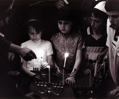 Hanukkah at Synagogue, Lansdowne Road, Hove: Children from the Synagogue's religion school light the first of the eight candles of Hanukkah, (festival of lights). A candle is lit every day of the festival to commemorate the rededication of the Temple at Jerusalem after the victory over the Syrians. | Reproduced with kind permission from Tony Tree
