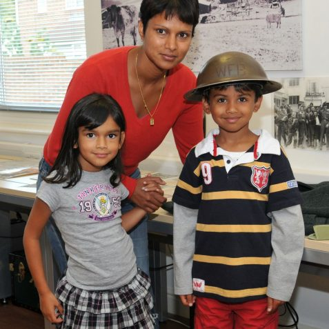 Mia and her Mum think Arvin looks great in his air-raid warden's hat | Photo by Tony Mould