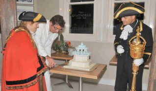 The Mayor of Brighton and Hove, Councillor Ann Norman, watched by the City Macebearer, Robert Robertson, cuts the celebration cake | Photo by Tony Mould
