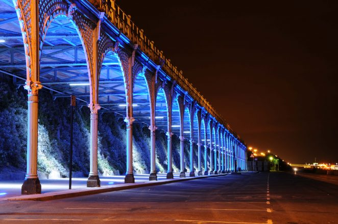 Brighton seafront with blue lights on the underwalk | Photo by James Willis