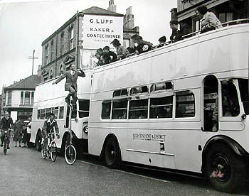 This photograph shows the famous Australian trick cyclist, Banner Forbut, promoting Tom Arnold's 1953 Ice Circus where he was appearing as a speciality act at the Sports Stadium in West Street, Brighton.  This photograph was taken in Hove and shows the open decked buses belong to the Brighton & Hove District Bus Company. The cream open top buses were a regular sight on Brighton seafront in the summer months.  In the background is the sign for G. Luff, baker and confectioner, this may give a better idea of the exact location of where this photograph was taken in Hove. | From the private collection of Trevor Chepstow