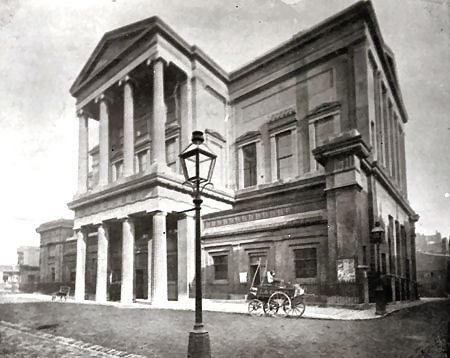 This photographic negative is a copy of an original negative. It shows Brighton Town Hall. It is a view south east of the front entrance. A gas lamp can be seen in the foreground of the image. A handcart bearing the name La Croix can also be seen in front of the town hall. | Reproduced courtesy of Royal Pavilion and Museums Brighton and Hove