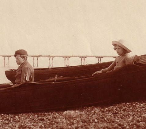 Boy and girl in boat in front of Palace Pier. Given the state of construction of the Pier, it looks as if this photo was taken in Victorian times. | This image is copyright of David Burgess.