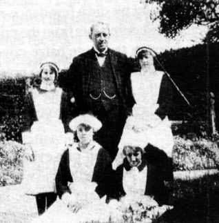 Daisy 'in service' at Ovingdean Hall. Pictured here (back left) with the Butler and some of the other girls on the staff. | Donated by Daisy Noakes