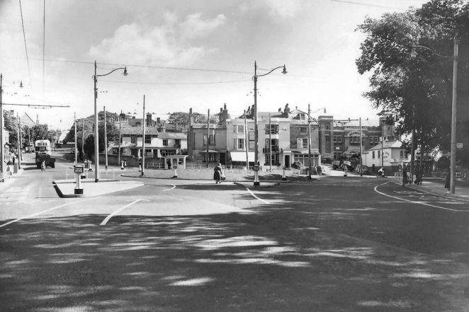 This is a photographic print made by the Borough Surveyor's department in July 1954. It shows Ditchling Road,  after road development work. New street lamps have been installed, and a new bus lane has opened on the left of the photograph. The Salvation Army Congress Hall can be seen in the background. | Royal Pavilion and Museums Brighton and Hove
