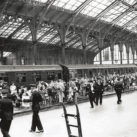September 1939: evacuees arriving at Brighton Station during Second World War. Crowds of children carrying gas masks can be seen gathered by a train, with numerous guards in attendance. | Reproduced courtesy of  Royal Pavilion, Libraries & Museums, Brighton & Hove