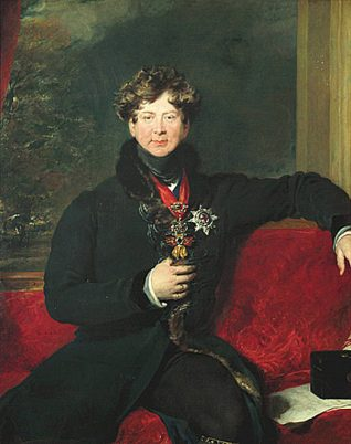 This is a half length portrait of George IV wearing a black coat with fur trimming, a medal and the Garter Star. He is sitting on a red couch with a black case and papers beside him. | Reproduced courtesy of Royal Pavilion, Libraries & Museums, Brighton & Hove