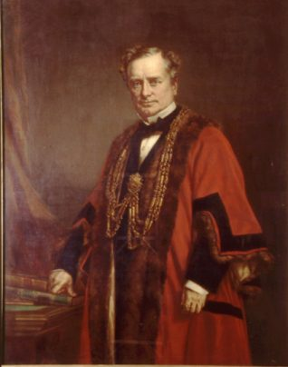 This painting three-quarter length portrait of Sir John Cordy Burrows in mayoral robes. His right hand rests on a pile of books on a desk. | Reproduced courtesy of Royal Pavilion, Libraries & Museums, Brighton & Hove