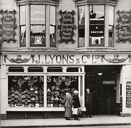 This is a photographic print of J. Lyons & Co's tea room at 14 North Street, Brighton. Two women can be seen admiring the large selection of cakes in the front windows. Signs in the upper storey windows indicate that this is the premises of R. Odinot's Hairdressing & Shaving Salon.  Joseph Lyons & Co. was one of the largest food manufacturers of the 1900s. The company's tea rooms were hugely popular, especially amongst the working classes. They were also known for the care taken in the design and decoration of their shops.  In spite of its success throughout much of the century, Lyons & Co's fortunes declined in the late 1960s. By the early 1980s, the company had been broken up and sold to various buyers. | Image reproduced with kind permission from Brighton and Hove in Pictures by Brighton and Hove City Council