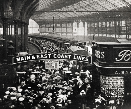 This photographic print is of Brighton Railway Station c1905. A large crowd are heading towards platform 3 to board the train there. A sign above them reads 'Main and East coast lines'.   Reproduced courtesy of Royal Pavilion, & Museums, Brighton & Hove