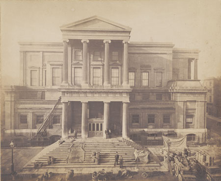 This photographic print shows the front entrance of Brighton Town Hall. A market can be seen at the foot of the steps. The ladder leading up to the balcony suggests that some construction work is taking place on the building.  The town hall is a prime example of neoclassical architecture in Brighton. Designed in 1830 by one of the town commissioners, Thomas Cooper, the building was strongly influenced by classical architecture. This photograph gives a clear view of the Ionic pillars surrounding the entrance. The interior also followed a similar design, with numerous Ionic and Corinthian columns. | Reproduced courtesy of Royal Pavilion and Museums Brighton and Hove