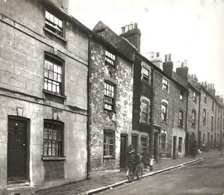 This is a photographic print of Richmond Hill, Brighton. It is a view northeast of several house fronts. Four pople can be seen standing in front of one of the doorways, while another figure is walking up the hill. A bicycle has been propped up against the kerb.  This photograph was commissioned by the Environmental Health department of Brighton Borough Council. It was intended to serve as part of a visual record of areas considered for slum clearance. Richmond Hill was demolished as part of the Morley Street redevelopment in the late 1930s. | Royal Pavilion and Museums Brighton and Hove