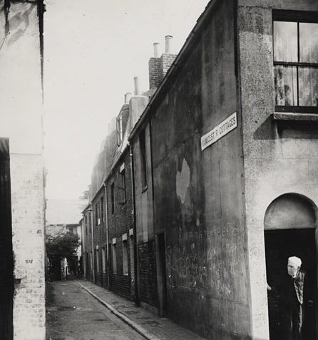 This is a photographic print of Gloucester Cottages, Brighton. It is a view looking north along the street. Graffiti can be seen on the wall of the house on the right hand side of the photograph. An old man can also be seen peering out of the doorway of this house.  This photograph was commissioned by the Environmental Health department of Brighton Borough Council. it formed part of a record of areas considered for slum clearance. Gloucester Cottages was demolished in the 1960s. | Reproduced courtesy of Royal Pavilion, Libraries & Museums, Brighton & Hove