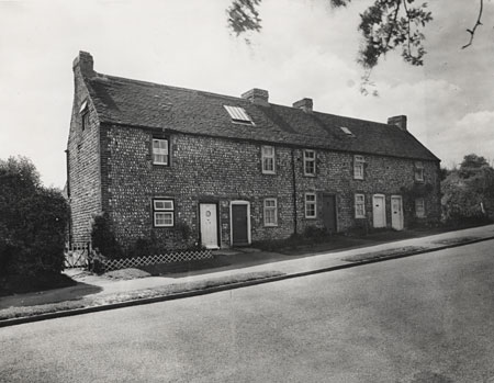 This is a photographic print of four cottages in Ladies Mile Road, Patcham, Brighton. It is a view of the front of these cottages, which eventually became 36-44 Ladies Mile Road.  This photograph was commissioned by the Environmental Health department of Brighton Borough Council. It formed part of a visual record of areas considered for slum clearance. Unusually, these cottages were not demolished after this photograph was taken, but were extensively altered and renumbered. | Reproduced courtesy of Royal Pavilion, Libraries & Museums, Brighton & Hove