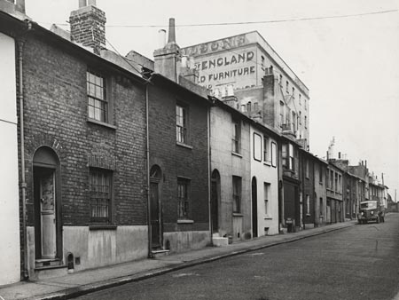 This is a photographic print of Blackman Street, Brighton. It is a view of the west side of the street, looking north. Hudson's furniture store is visible behind the houses.  This photograph was commissioned by the Environmental Health department of Brighton Borough Council. It formed part of a visual record of areas considered for slum clearance. Blackman Street was acquired by the Council under a {g:Compulsory Purchase Order}Compulsory Purchase{/g} order in 1959. These houses were demolished in 1962. | Reproduced courtesy of Royal Pavilion, Libraries & Museums, Brighton & Hove