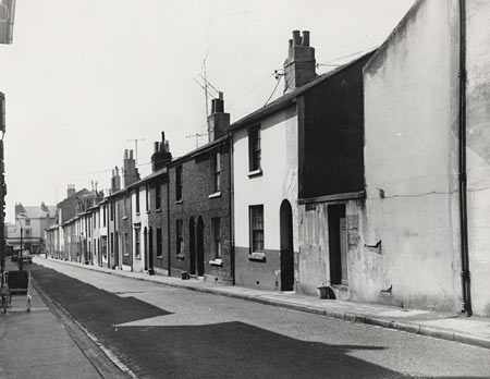 This is a photographic print of the west side of Wood Street, Brighton. It is a view along the street showing the fronts of the houses.  This photograph was commissioned by the Environmental Health department of Brighton Borough Council. It formed part of a visual record of buildings and areas that were considered for slum clearance. Wood Street was demolished in 1962. | Reproduced courtesy of Royal Pavilion, Libraries & Museums, Brighton & Hove