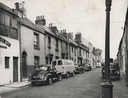 This is a photographic print of Whitecross Street, Brighton. It is a view of the west side of the street in which numerous parked cars can be seen. This photograph was commissioned by the Environmental Health department of Brighton Borough Council. It formed part of a visual record of areas considered for slum clearance. Whitecross Street ran between Trafalgar Street and Cheapside. Much of it was demolished in 1962. | Reproduced courtesy of Royal Pavilion, Libraries & Museums, Brighton & Hove