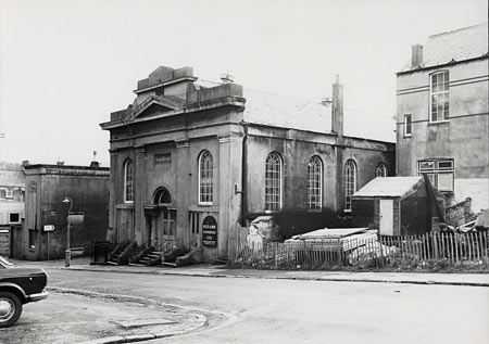 This photographic print was made by the Borough Surveyor's department. It shows a view of Ann Street, Brighton, looking southeast. The building in the centre of the picture was formerly the London Road Chapel. It was built in 1830 for the Countess of Huntingdon's Connexion, a non-conformist faith closely allied with Methodism. The building was enlarged in 1857, but had ceased to serve as a place of worship by 1961 when it had become a warehouse. The building was demolished in 1976, three years after this photograph was taken. | Reproduced courtesy of Royal Pavilion, Libraries & Museums, Brighton & Hove