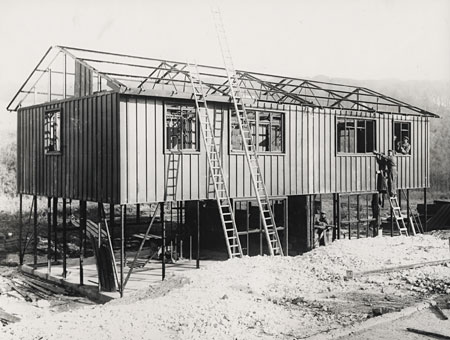 This photographic print shows men working on prefabricated housing in Parkside Estate, Coldean. It was made by the Borough Surveyor's department in December 1946. Many of the workers were only trainees due to a lack of expert builders after WW2. They were designed to only last for 15 years, but many are still in use today. | Reproduced courtesy of Royal Pavilion, Libraries & Museums, Brighton & Hove