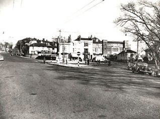 This photographic print shows Ditchling Road by the open market in Brighton. A Salvation Army building can be seen in the background. The print was made by the Borough Surveyor's department in October 1953. | Image reproduced with kind permission of The Royal Pavilion and Museums Brighton and Hove