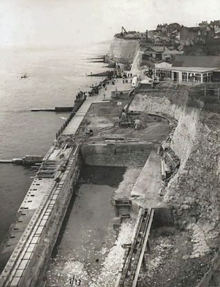 This photographic print was made by the Borough Surveyor's department in July 1932. It is a view west of Rottingdean seafront. Construction work on the Rottingdean bathing pool can be seen in the bottom half of the photograph.  The photograph was taken as part of a series recording work on improving sea defences in the area between Rottingdean and Saltdean. Designed by the Borough Engineer, David Edwards, these defences became part of the Undercliff Walk that runs east from Black Rock. | Reproduced courtesy of Royal Pavilion & Museums, Brighton & Hove