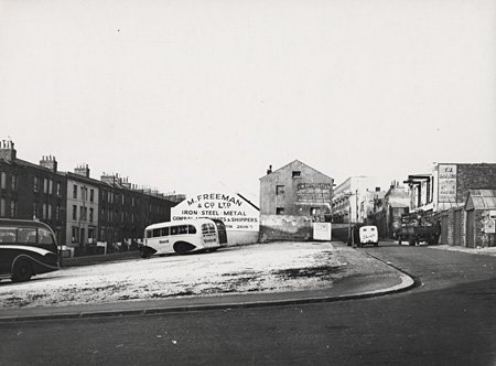 This photographic print was made by the Borough Surveyor's department in October 1954. It shows the corner of Edward Street and John Street, Brighton. Three buses canbe seen in a car park on the left of the photograph. In 1965 the police station opened on this site. The building was designed by Percy Billington, the Borough Surveyor. | Reproduced courtesy of Royal Pavilion, Libraries & Museums, Brighton & Hove