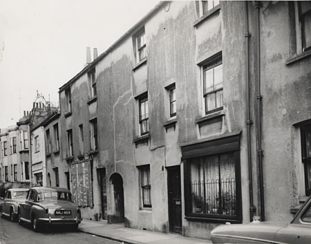 This is a photographic print of Gloucester Street, Brighton. It is a view along the street, focusing on several houses that were considered for demolition. One house has the front window boarded up, while another has metal bars in front of the window. All these houses show signs of damp.  This photograph was commissioned by the Environmental Health department of Brighton Borough Council. It formed part of a visual record of areas considered for slum clearance. These buildings were probably demolished in the late 1950s. | Reproduced courtesy of Royal Pavilion, Libraries & Museums, Brighton & Hove