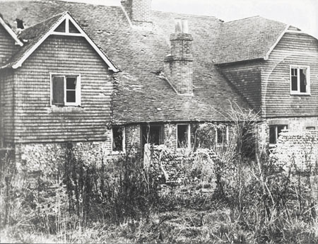 This photographic print shows cottages 3 and 4 on the Stanmer Estate, Brighton. It is a view of the rear of the cottages, showing overgrown vegetation in the foreground.  The photograph was commissoned by the Borough Surveyor's department of Brighton Borough Council. It was amongst a number taken of the area which were presumably used to survey the condition of the buildings prior to their demolition. | Reproduced courtesy of Royal Pavilion and Museums Brighton and Hove