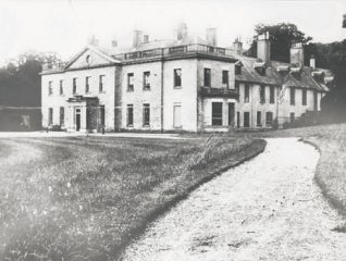 c1932 This photographic print shows Stanmer House, Brighton. It is a view of the corner of the building, showing its front entrance. The path leading to the house can be seen in the foreground.  The photograph was commissoned by the Borough Surveyor's department of Brighton Borough Council. It was amongst a number taken of the area which were presumably used to survey the condition of the buildings. | Reproduced courtesy of Royal Pavilion & Museums, Brighton & Hove