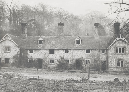 This photographic print shows several cottages on the Stanmer Estate, Brighton. The cottages are clearly in a derelict state.  The photograph was commissoned by the Borough Surveyor's department of Brighton Borough Council. It was amongst a number taken of the area which were presumably used to survey the condition of the buildings. | Reproduced courtesy of Royal Pavilion and Museums Brighton and Hove