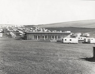 This photographic print shows the Recreation Hall of the Municipal Camping and Caravan Ground in Sheepcote Valley, Brighton. A number of caravans can be seen surrounding the hall.  This photograph was produced by the Borough Surveyor's department. It was presumably taken as a record of the camp site's facilities. The site had opened on 14 May 1938, just one year before this photograph was taken. It was the first local authority owned camp site in Britain. It used a number of buildings that had previously been part of Newhouse Farm. The Recreation Hall was developed from an original flint barn. | Reproduced courtesy of Royal Pavilion and Museums Brighton and Hove