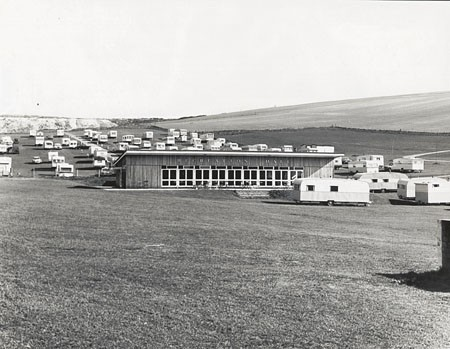 This photographic print shows the Recreation Hall of the Municipal Camping and Caravan Ground in Sheepcote Valley, Brighton. A number of caravans can be seen surrounding the hall. This photograph was produced by the Borough Surveyor's department. It was presumably taken as a record of the camp site's facilities. The site had opened on 14 May 1938, just one year before this photograph was taken. It was the first local authority owned camp site in Britain. It used a number of buildings that had previously been part of Newhouse Farm. The Recreation Hall was developed from an original flint barn. | Royal Pavilion and Museums Brighton and Hove