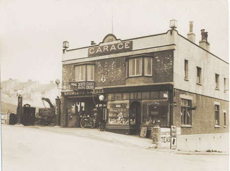 This photographic print shows Bromley's Garage in Roedean Road, Brighton. It is a view of the front of the building, with a tea room visible on the right of the building. A sign at the top of the building indicates that it was built in 1926.  The reverse of the print bears a photographer's stamp. A partially legible pencil note on the front of the photograph states 'Petrol Pumps In Ch-'. | Reproduced courtesy of Royal Pavilion, & Museums, Brighton & Hove