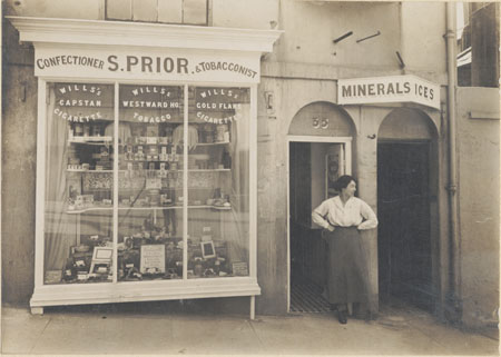 This photographic print shows S. Prior's Confectioner & Tobacconist's store at 35 Spring Street, Brighton. A woman can be seen standing in the ship doorway, looking left. | Reproduced courtesy of Royal Pavilion and Museums Brighton and Hove