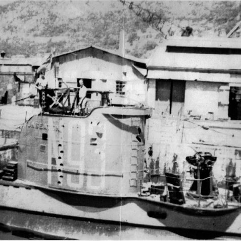 H.M.S.  Unbeaten alongside in Gibraltar during her voyage home to the UK for refit in August 1942. The ship's 'Jolly Roger' is being displayed by some crew members on the conning tower.  The letters on the side of the conning tower read 'N93' her pennant number. | Photo: From the private collection of Mrs B. Woodward.