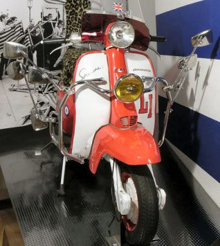 Lambretta Li 150 motor scooter, c1963, with a red and white livery steel body, which also features Union flag and classic mod target symbols. The seat is covered with an artificial leopard print fur cover. The scooter has extra outrider wing mirrors attached to the front and a Union flag is mounted on the aerial at the rear of the scooter. | Royal Pavilion & Museums, Brighton & Hove