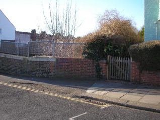 Poorly matching brickwork hides the entrance to Holland Road Halt | From the private collection of Peter Groves