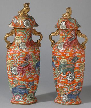 This pair of vases each have a fluted, oval body, narrow neck and a pair of gilded handles in the forms of fish. The lids are domed with a gilded knop in the form of a dog. Both the vase and its lid are decorated overall in enamel colours with a design of dogs holding stems of flowers in their mouths amidst swirling clouds, all against a bright orange ground. There are underglaze blue reign marks on the bases which may refer to the Qing Dynasty emperor Jiaqing. | Reproduced courtesy of Royal Pavilion, & Museums, Brighton & Hove