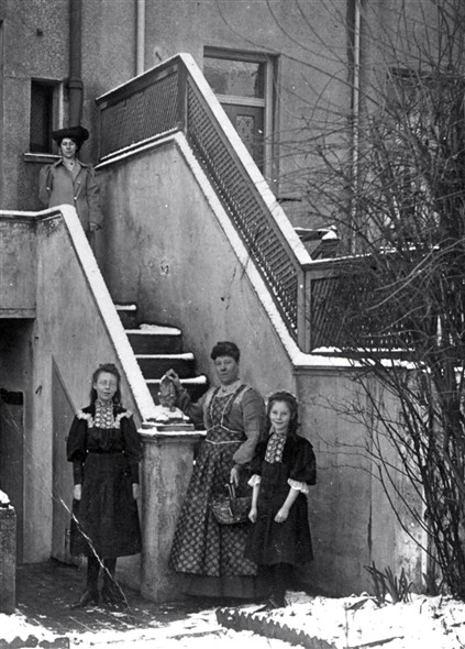 This photo taken at the back of the Powell family home in 1908 shows Florence May Powell with her sister Edith Rose Powell standing at the bottom of the steps . Their mother Sarah Powell (nee) Bishop Sarah the eldest daughter stands at the top of the steps   From the private collection of Elizabeth Wickstead