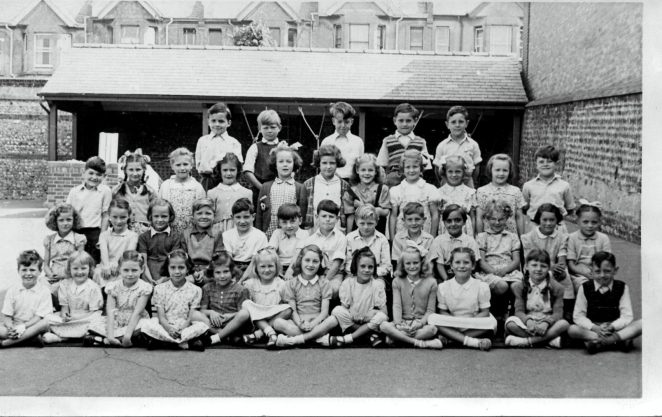 This photo is taken in the School playground.You may just see the brick of the air raid shelter at the rear of the right side.The children are as follows:Back row L to R: n/k, Alan Johnson, Philip Cook, n/k, David Housego. 2nd Row; Brian Evans,Christine Goble, Pauline Robinson, Margaret Ratcliffe, Beverley Jarvis, Judy Bolton, n/k, Brenda Taylor, Susan Baker, Joy Chapman, Bob Ducharme. 3rd Row: n/k, Pamela Warburton, Evelyn Hawkes, George Beard, Clive Boyle, Dennis Parrett, Norman Farrar, n/k, Paul Holcombe, John Marchant, Pat Brain, Veronica, Pamela Betts. Front Row: Barbara Paine, Marion Tipple, Margaret Holden, n/k, n/k, Audrey?, Betty Ball, n/k, Rita Marsh, Carol?, Frank Heath. | From the private collection of Dennis Parrett