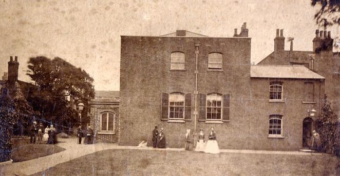 Quaker Meeting House, Brighton, 1875. Taken previous to alterations made in 1875. Below are the names of the groups of people from left to right. (This is the caption on the front of photograph. There is another caption on the back, but this one seems to tally with the number of figures.) | Photo submitted to the website by Tony Tree