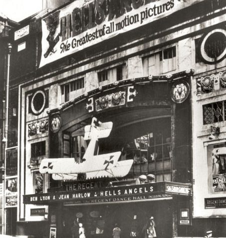 This black and white photographic print shows the front of the Regent cinema in Queen's Road, Brighton. The top of the building is covered by a large banner advertising 'Hell's Angels', an early 'talkie' film. A Tiger Moth aeroplane has been suspended above the entrance. | Image reproduced with kind permission of The Royal Pavilion and Museums Brighton and Hove